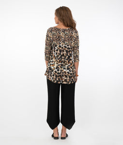 brunette model in a safari print top with black pants in front of a white background