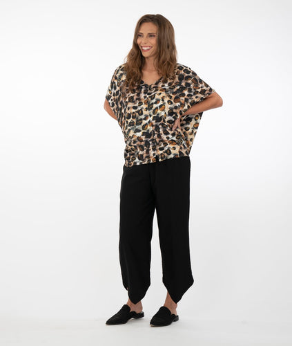 brunette model wearing an animal print top with black pants in front of a white background