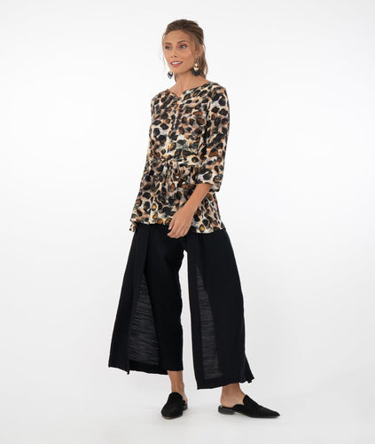 model in an animal print top with a tie at the waist, worn with black pants in front of a white background
