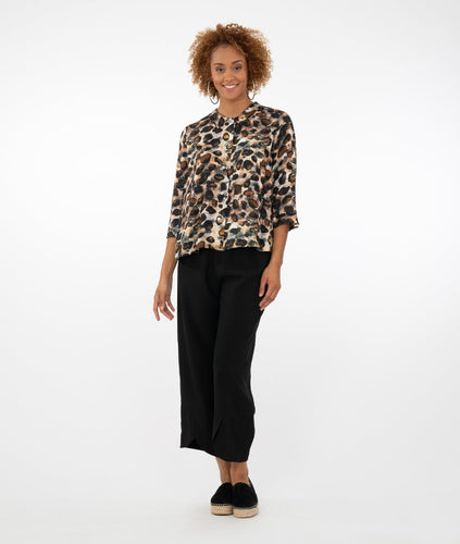 model in an animal print button up blouse with black pants in front of a white background