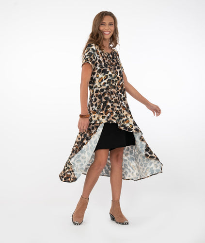 brunette model wearing black shorts with a long animal print tunic with a short front and long back, in front of a white background