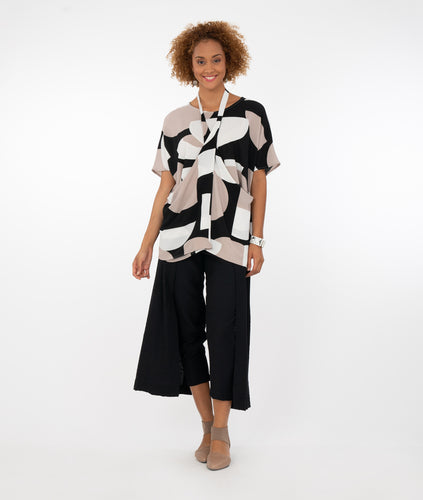model in a black pant with flowing side panels, worn with a black, white and taupe print top with two side panels joined by a strap, worn around the neck halter style