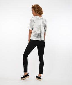 model in a white button up top with black and gray print, with black pants in front of a white background