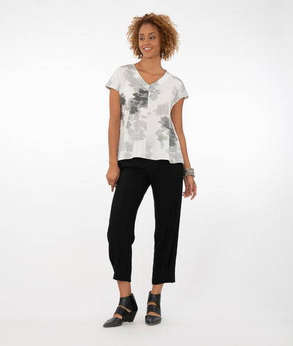 model in a white top with black and gray print, with black pants in front of a white background