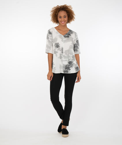model in a white top with black and gray print, with black leggings in front of a white background
