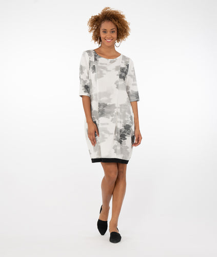 model in a white dress with black and gray print and a black band at the hemline, in front of a white background