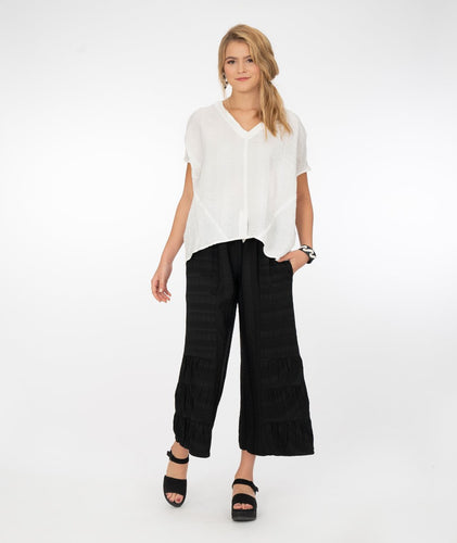 model in a loose fitting pull over white top, with black pants with a pleated detail at the bottom hem, in front of a white background