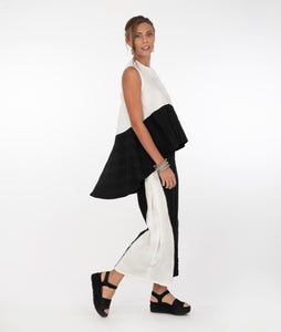 model in a flowy tank top that is white on top with a black asymmetrical bottom, and a pant that is black with a white panel on the side, in front of a white background