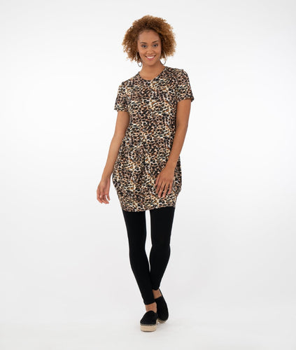 model wearing an animal print tunic with one front pocket. worn with black leggings in front of a white background