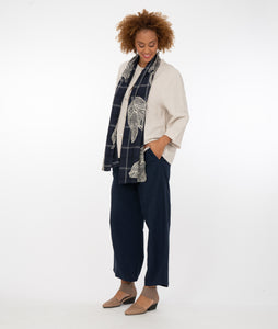 model in a bone color button up top with a blue scarf, navy pants in front of a white background