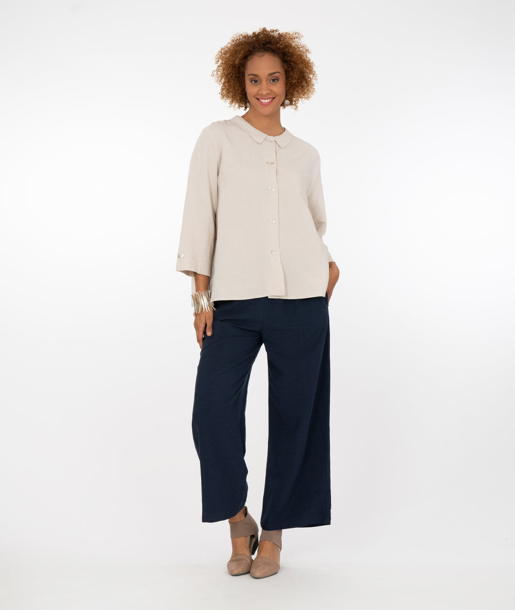 model in a bone color button up top with navy pants in front of a white background