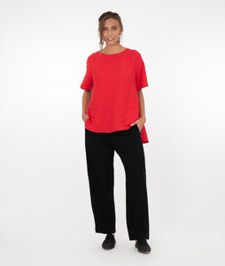 model in a red pull over top with a hi-lo hemline, with black pants in front of a white background