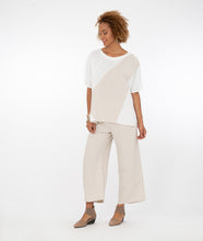 Load image into Gallery viewer, model in a white and bone color blocked top with matching bone pants, in front of a white background