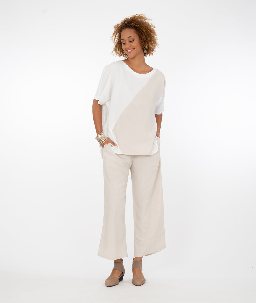 model in a white and bone color blocked top with matching bone pants, in front of a white background