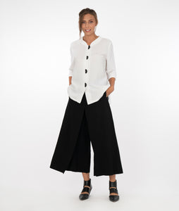 model in a white button up top with large black buttons, with wide leg black pants with a layered piece in the front, standing in front of a white background