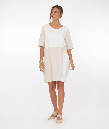 model in a white and bone colored color blocked tunic