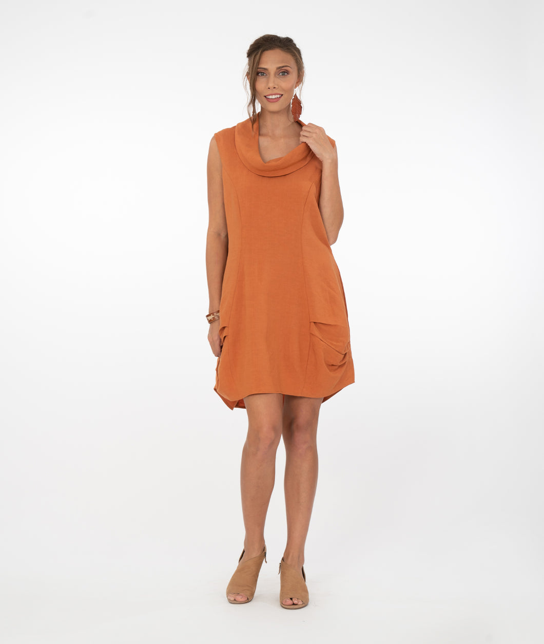model in a rust colored sleeveless tunic with a cowl neck and pleats at the bottom hem