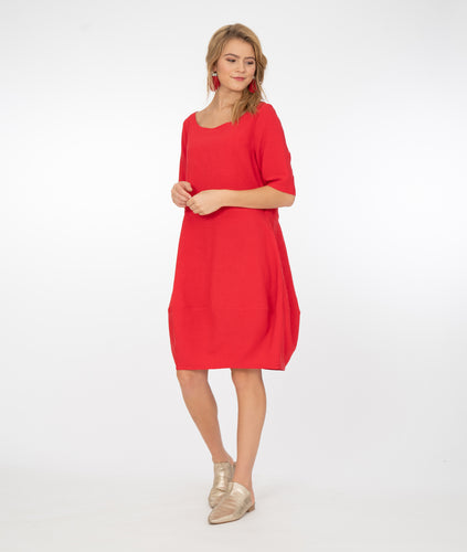 model in a red tunic dress in front of a white background
