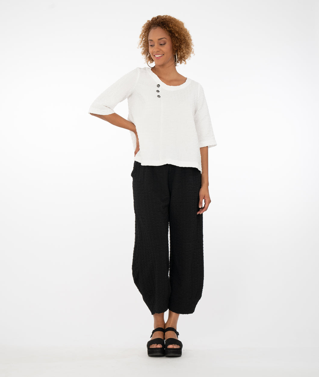 model in a white textured top with three buttons at the neckline, off centered, paired with textured black pants and standing in front of a white background