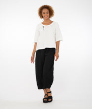 Load image into Gallery viewer, model in a white textured top with three buttons at the neckline, off centered, paired with textured black pants and standing in front of a white background