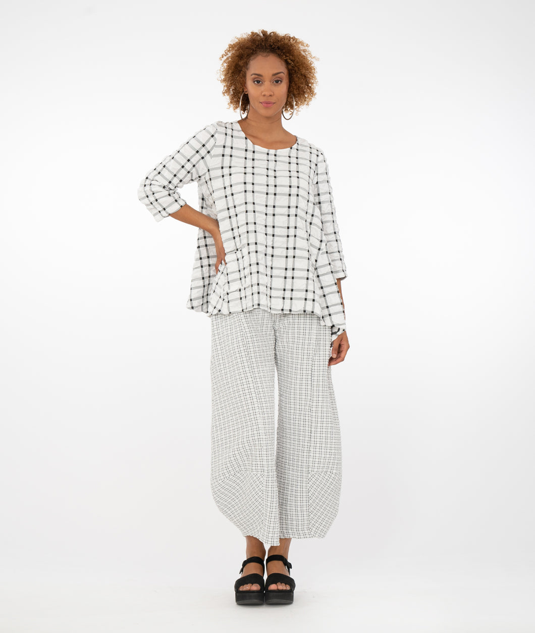 model in a black/white grid patterened top with pants in the same, but small print, in front of a white background