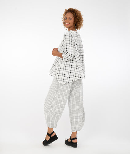 model in a large black and white grid print top with small grid print black and white pants, in front of a white background