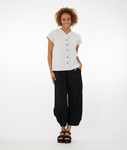 model in a black and white grid patterned button up top with a black textured pant, in front of a white background