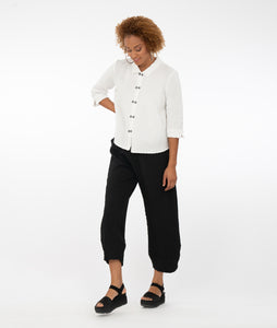 model in a white textured button up top, paired with textured black pants and standing in front of a white background
