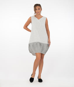 model in a black and white grid print tunic with a contrasting hem, in front of a white background
