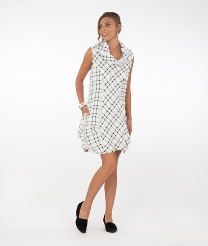 model in a black and white grid patterened tunic with pleats at the hips and a cowl neck, standing in front of a white background