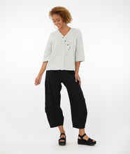 Load image into Gallery viewer, model in a black and white grid patterened top with buttons along a diagonal placket at the center front seam, worn with textured black pants, standing in front of a white background