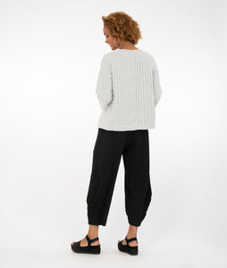 model in a black and white grid patterened top with buttons along a diagonal placket at the center front seam, worn with textured black pants, standing in front of a white background