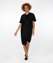 Load image into Gallery viewer, model in a black tunic with a halter style strap at her neck