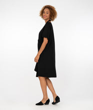 Load image into Gallery viewer, model in a black tunic with a halter styled strap connecting the sides, standing in front of a white background