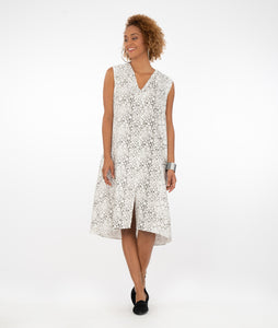 model in a bubble print sleeveless dress with a v-neck and split at the bottom of the front center seam, standing in front of a white background