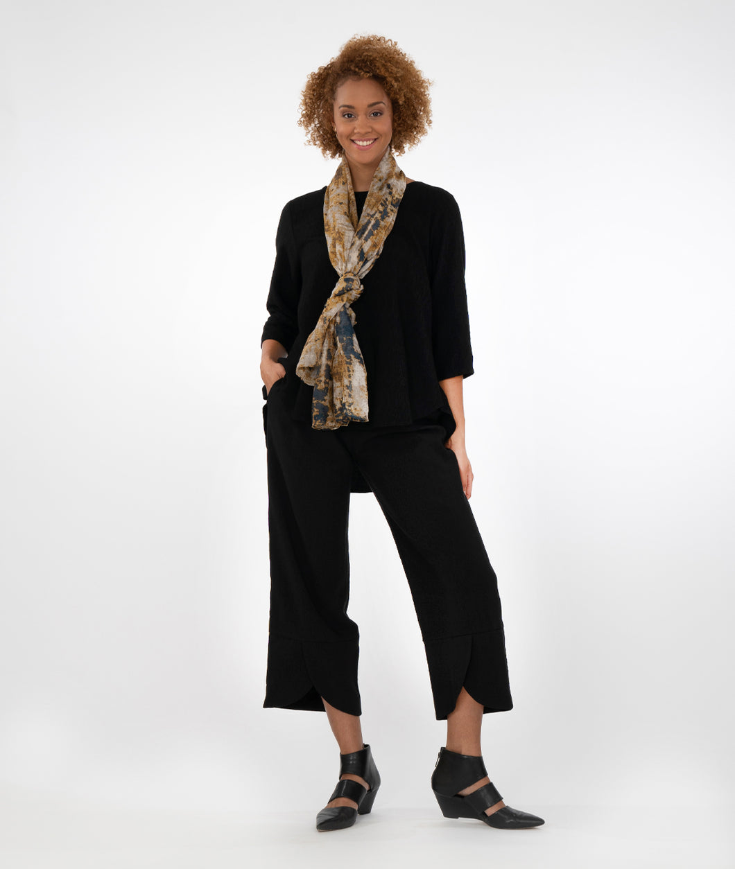 model in a black top with a multicolored scarf, worn with black pants with a curved overlay at the hem, standing infront of a white background