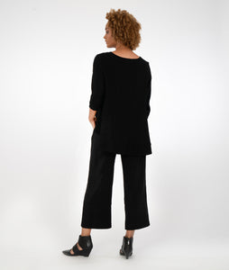 model in a black top, worn with black pants with a curved overlay at the hem, standing infront of a white background