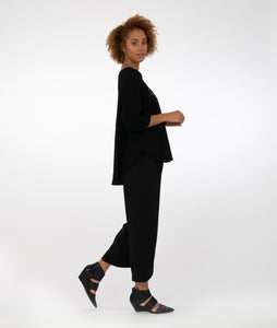 model in a black wide leg pant with a black top with a full wavy body