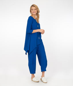 model in electric blue button up top with a matching pant with a tall cuff, in front of a white background