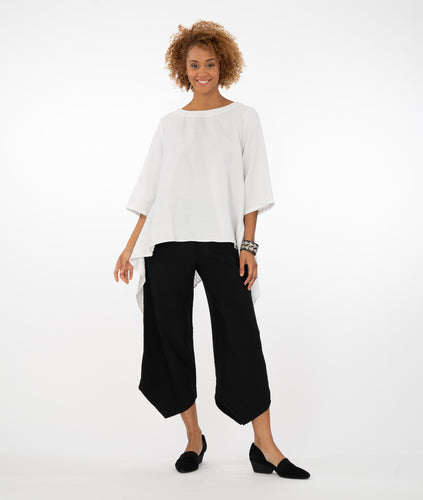model in a white top with black pants, both with pointed hemlines, infront of a white background