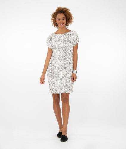 model in a white dress with a bubble print, standing in front of a white background