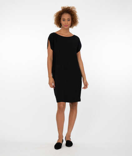 model in a black shift dress with a rounded split on each sleeve
