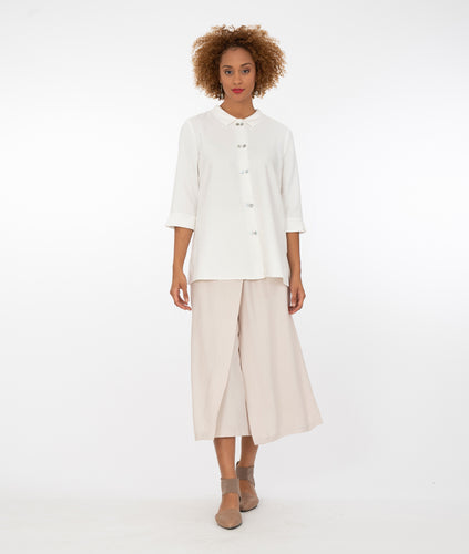 model in a long white button up blouse with wide leg khaki pants, in front of a white background