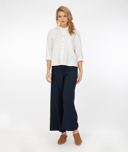 model in a navy wide leg pant with a white button up blouse