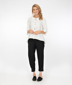 model in black pants with a white button up jacket, in front of a white background