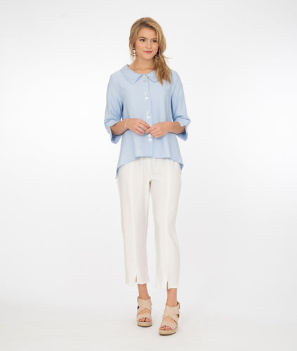 model in a powder  blue button up top with a white pant with center seams on each leg, with a split at the ankle, standing in front of a white background