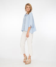 Load image into Gallery viewer, model in white pants with a powder blue button up jacket
