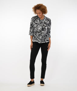 model in a black and white patterened button up top with black leggings in front of a white background