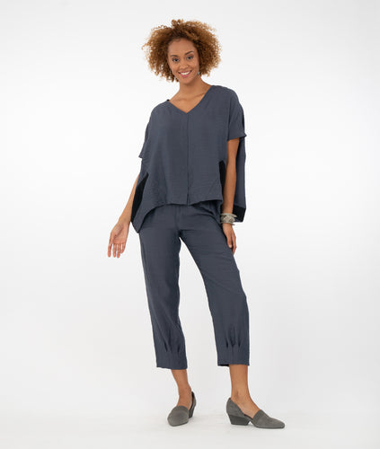 model in iron color pants with an matching shirt with a black stripe on the side. Standing in front of a white background.