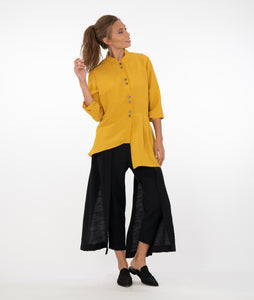 model in a saffron button up top with a slim black pant with wide panels hanging down